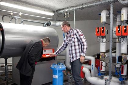 deux hommes contrôlent une installation thermique