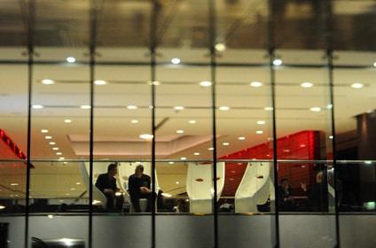 deux hommes discutent dans un immeuble de bureaux éclairé